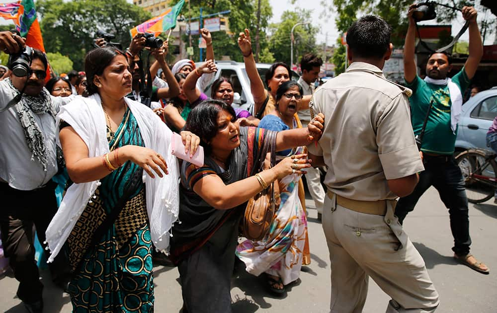 A Bharatiya Janata Party (BJP) member pushes aside a policeman blocking the path during a protest against the gang rape of two teenage girls, in Allahabad.