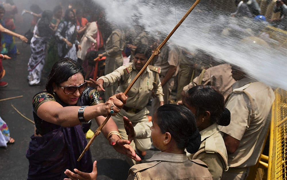 A woman, one among the protestors demonstrating outside the office of Uttar Pradesh state chief minister Akhilesh Yadav, demanding that he crack down on an increasing number of rape and other attacks on women and girls, scuffles with police in Lucknow.