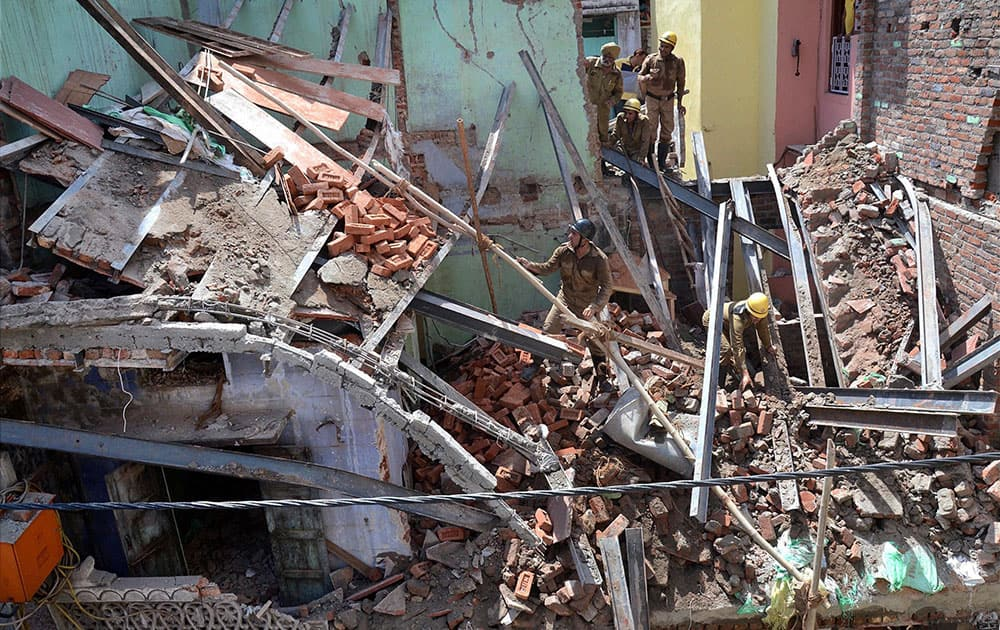 Rescuers search among the debris after a three-story building under construction collapsed in Sadar Bazar area of New Delhi.