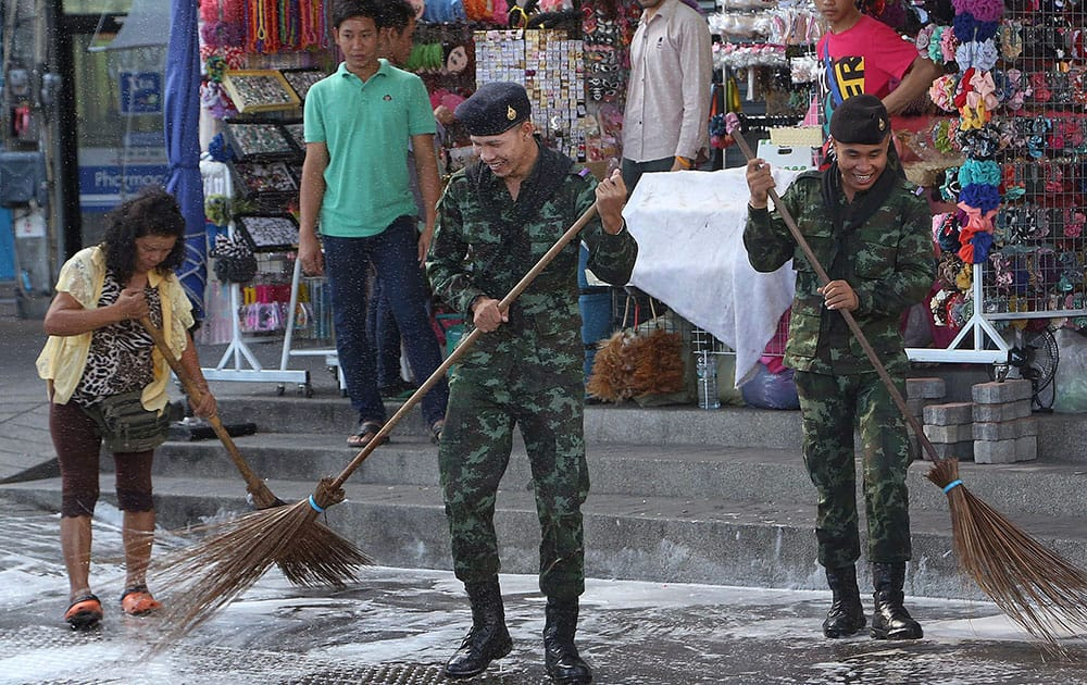 Thai soldiers and city workers sweep the ground during a big cleaning joint operation at Victory Monument in Bangkok.