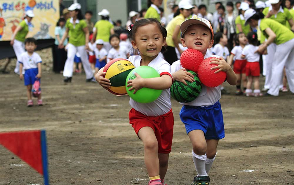 Children carrying balls run in a game during an International Children`s Day event at Pyongyang September 15 Nursery in Pyongyang, North Korea.