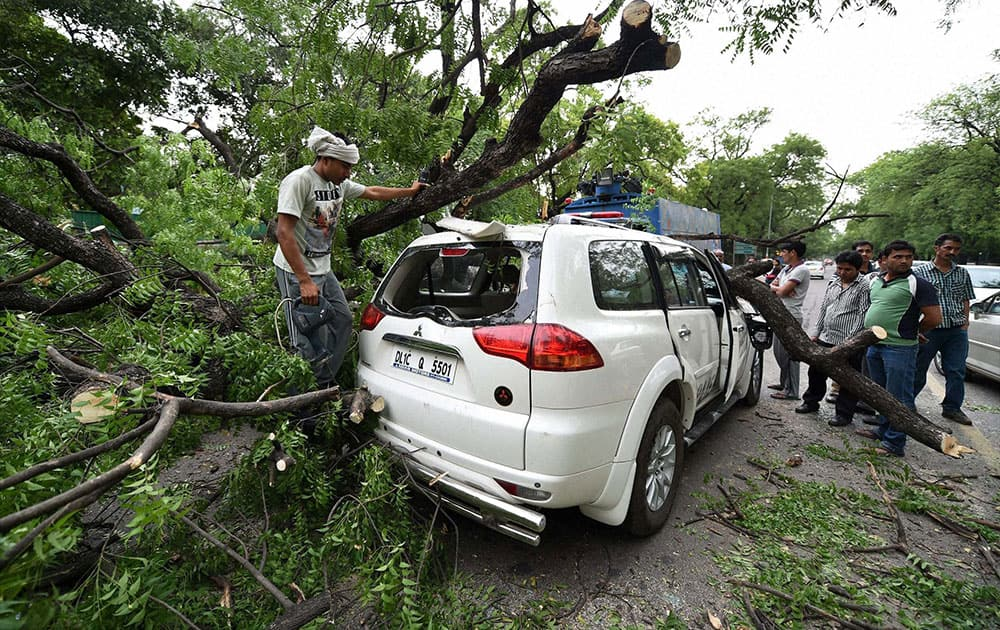 A tree branch fell on a car near Gymkhana Club after a storm accompanied by dark clouds in New Delhi.