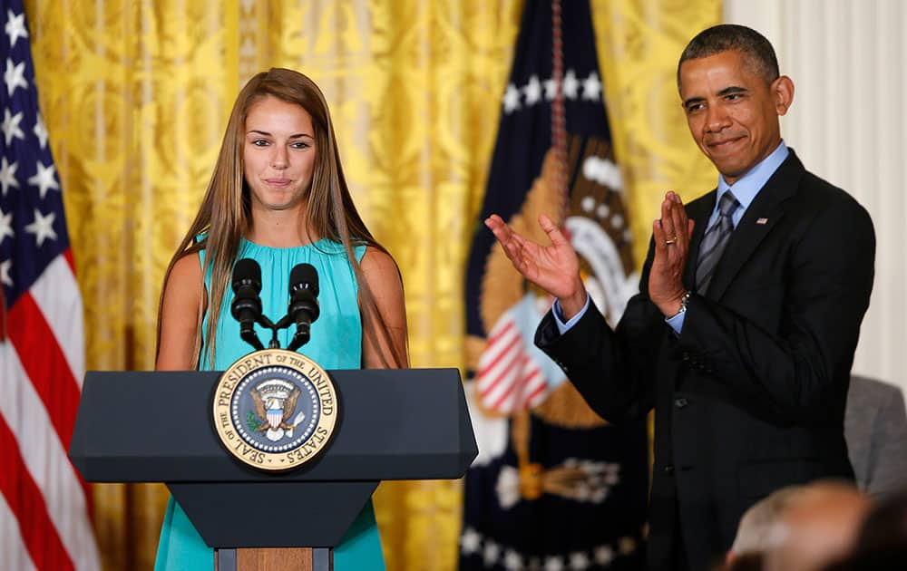 President Barack Obama applauds Victoria Bellucci, a 2014 graduate of Huntingtown High Shool in Huntingtown, Md., who suffered five concussions playing soccer, in the East Room of the White House in Washington, during the White House Healthy Kids and Safe Sports Concussion Summit.