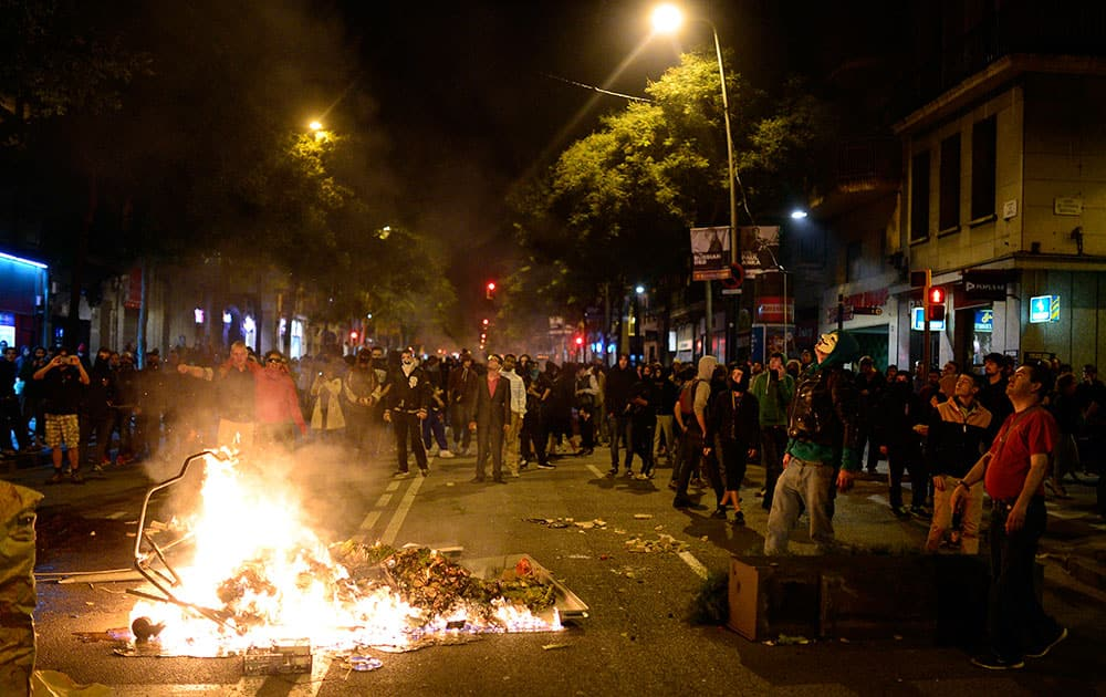 Demonstrators make a barricade with a burning containers during a protest against the eviction of social squatters from the building in Barcelona, Spain.