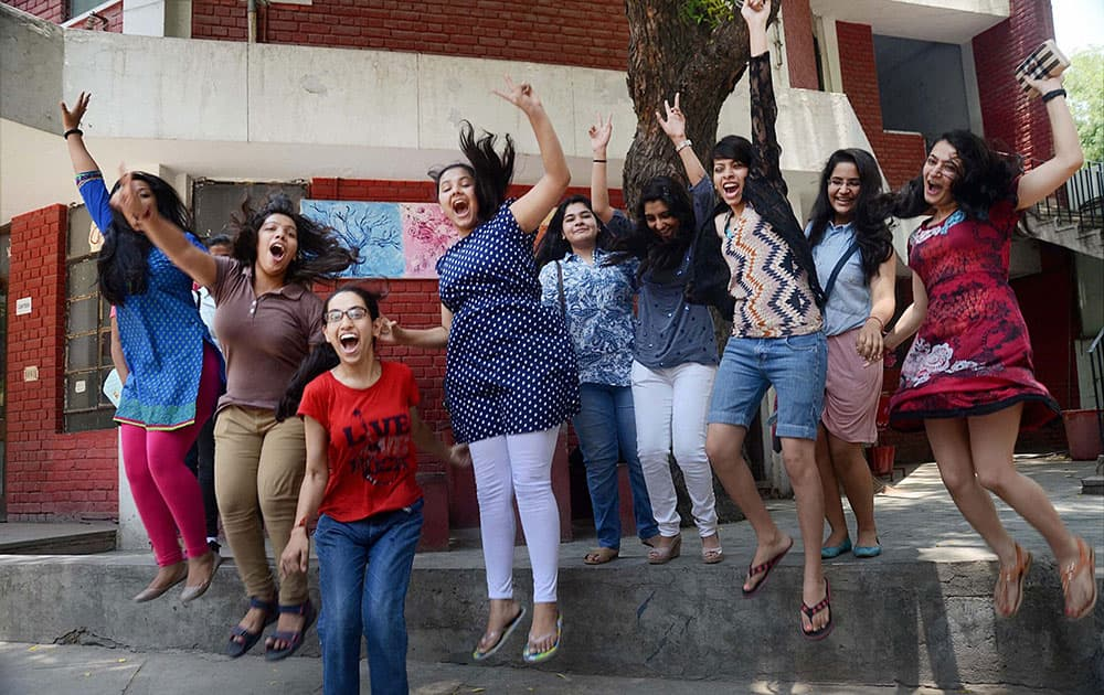 Students celebrate their success after announcement of CBSE class 12th results, at their school in New Delhi.