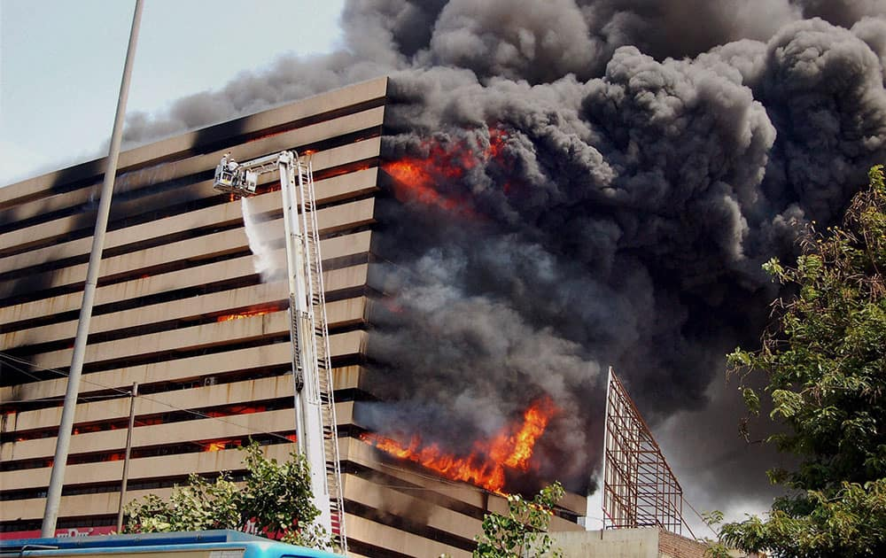 Fire fighters try to control fire that broke out in a multi-storey building in Surat.