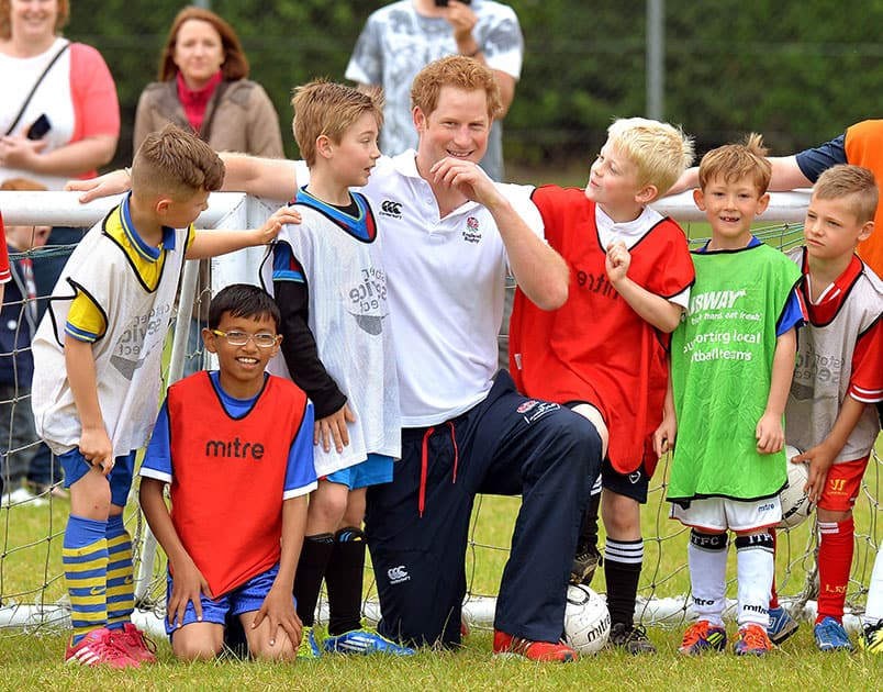 Britain`s Prince Harry poses with boys after a short soccer kick about at the Inspire Suffolk centre for young people in Ipswich, eastern England.