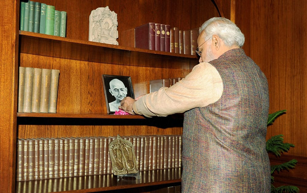 Prime Minister Narendra Modi paying tribute to Mahatma Gandhi after taking charge of the office at PMO in New Delhi.