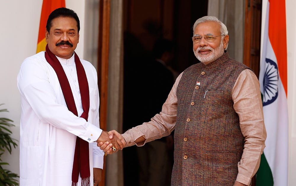 Prime Minister Narendra Modi shakes hand with Sri Lankan President Mahinda Rajapaksa before the start of their meeting in New Delhi.