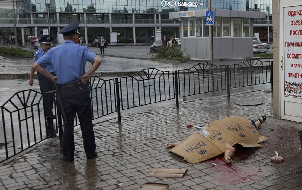 Police officers stand next to a body of an unidentified woman killed by shrapnel following a shelling from Ukrainian government forces, outside railway station in Donetsk, Ukraine.