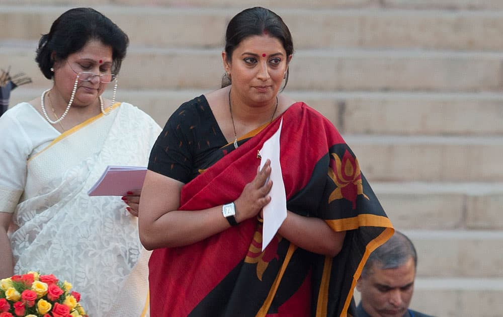 Smriti Irani greets the audience after she takes the oath of office at the presidential palace in New Delhi.