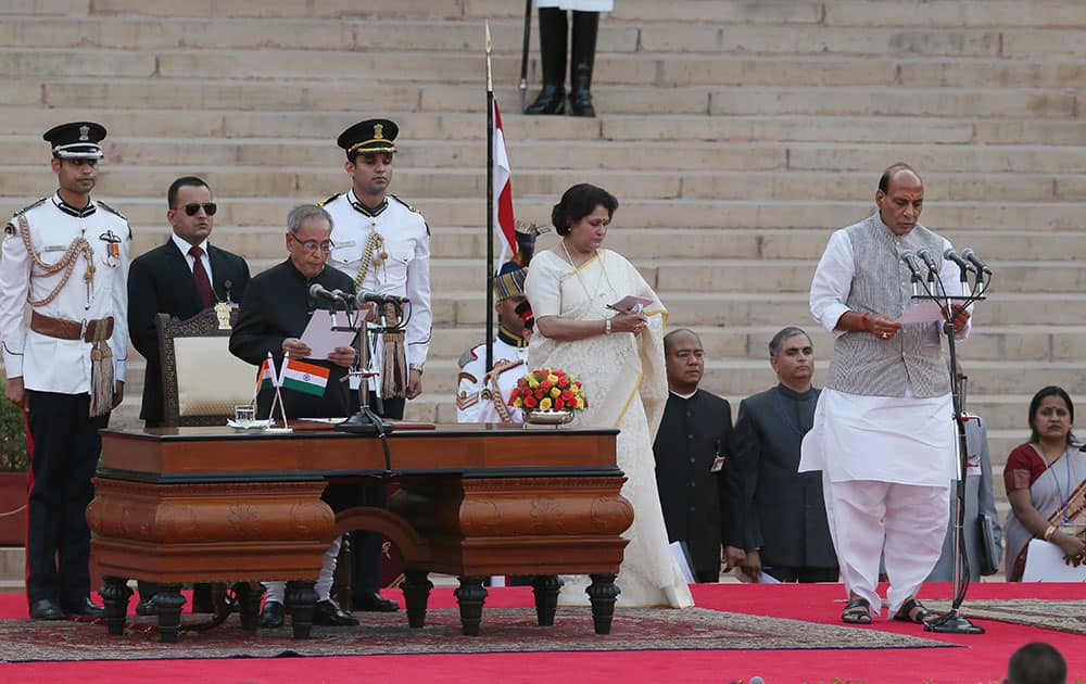 President Pranab Mukherjee, third left, administers the oath of office to Cabinet Minister Rajnath Singh, right, at the presidential palace in New Delhi.