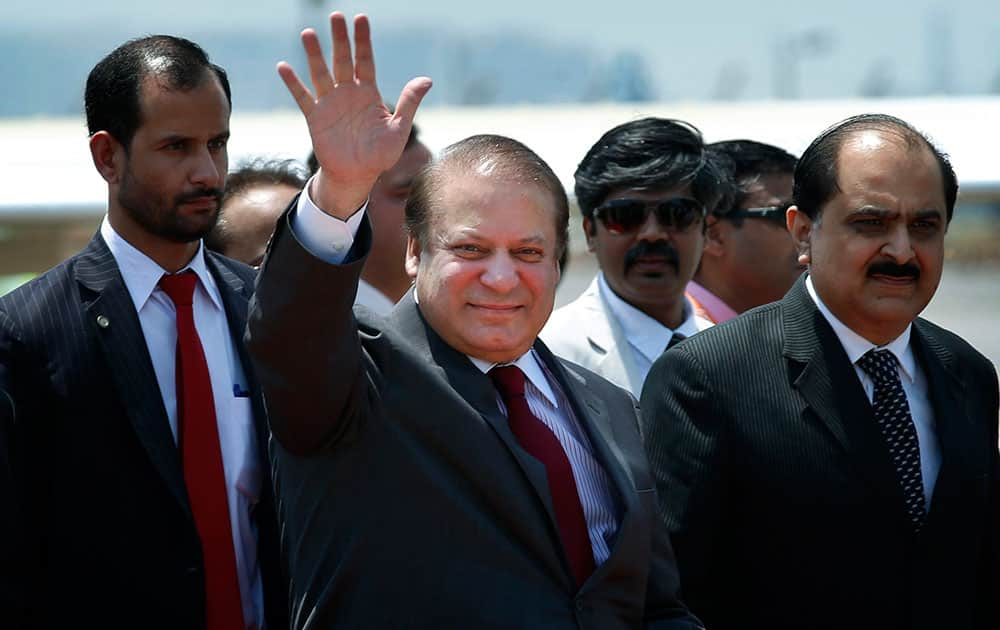 Pakistani Prime Minister Nawaz Sharif waves as he arrives to attend the swearing in ceremony of India's prime minister elect Narendra Modi in New Delhi.