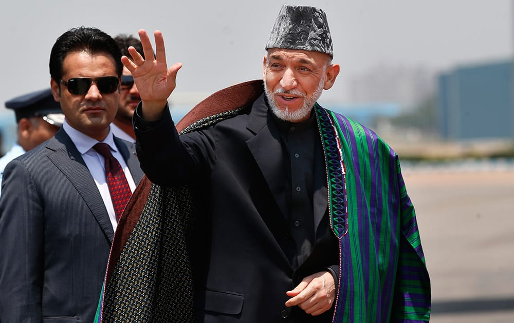 Afghan President Hamid Karzai waves upon arrival for the swearing in ceremony of India`s prime minister elect Narendra Modi in New Delhi.