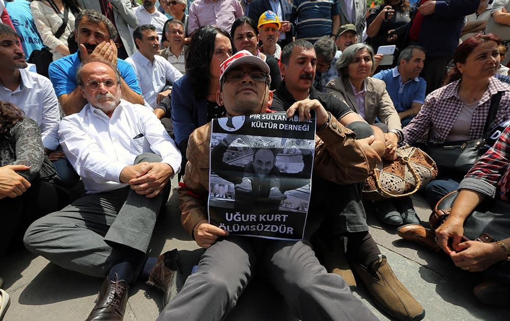 People sit to protest the killing of Ugur Kurt in Ankara, Turkey.