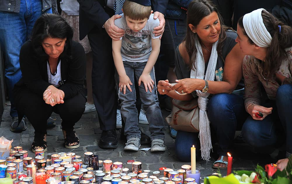 A boy looks at candles and flowers at the entrance of the Jewish museum in Brussels.