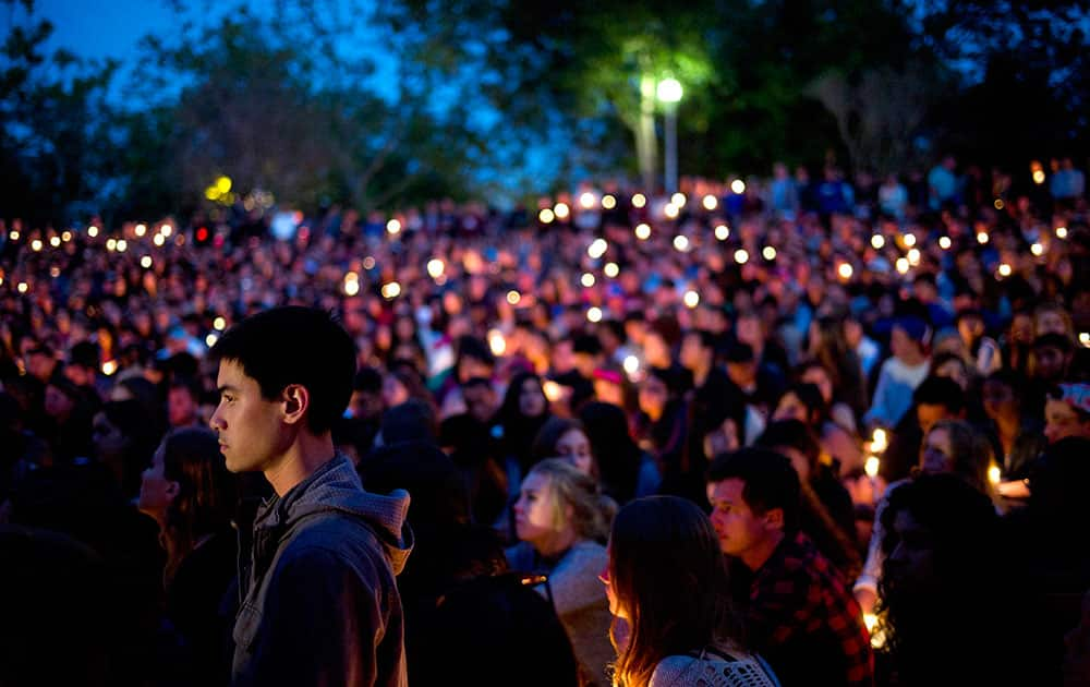 People gather at a park for a candlelight vigil to honor the victims of Friday night`s mass shooting in Isla Vista, Calif.