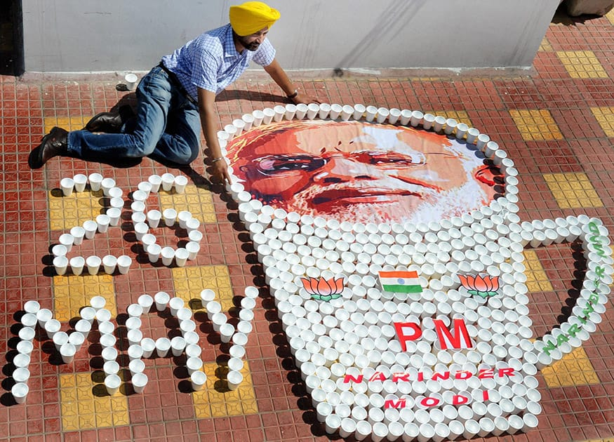 A miniature artist creates a picture of Prime Minister-designate Narendra Modi with glasses used for serving tea to congratulate him ahead of his swearing-in ceremony, in Amritsar.