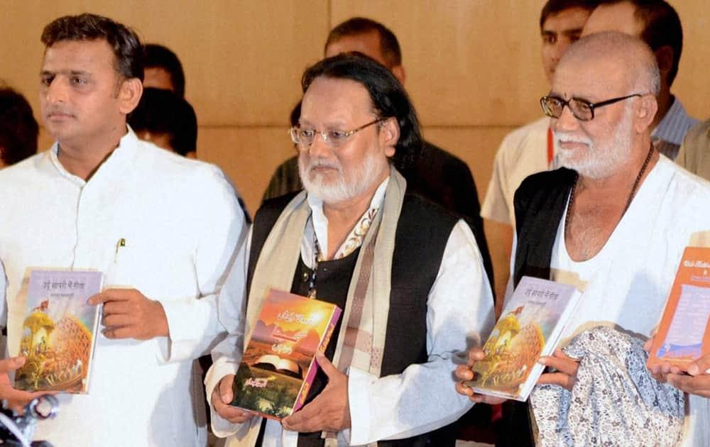 Uttar Pradesh Chief Minister Aklhilesh Yadav with spiritual preacher Morari Bapu (right) and author Anwar Jalalpuri releasing the latter`s book `Urdu Shayari me Geeta` in Lucknow.