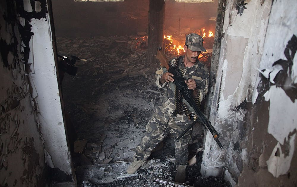 An Afghan soldier takes position at the site of a clash between insurgents and security forces at the Indian Consulate in Herat, Afghanistan.
