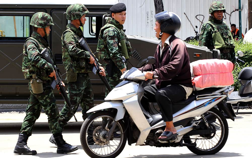 A motorcyclist rides past Thai soldiers patroling on a street in Bangkok, Thailand. Thailand`s ruling military on Friday summoned the entire ousted government and members of the politically influential family at the heart of the country`s long-running conflict, a day after it seized control of this volatile Southeast Asian nation in a non-violent coup.