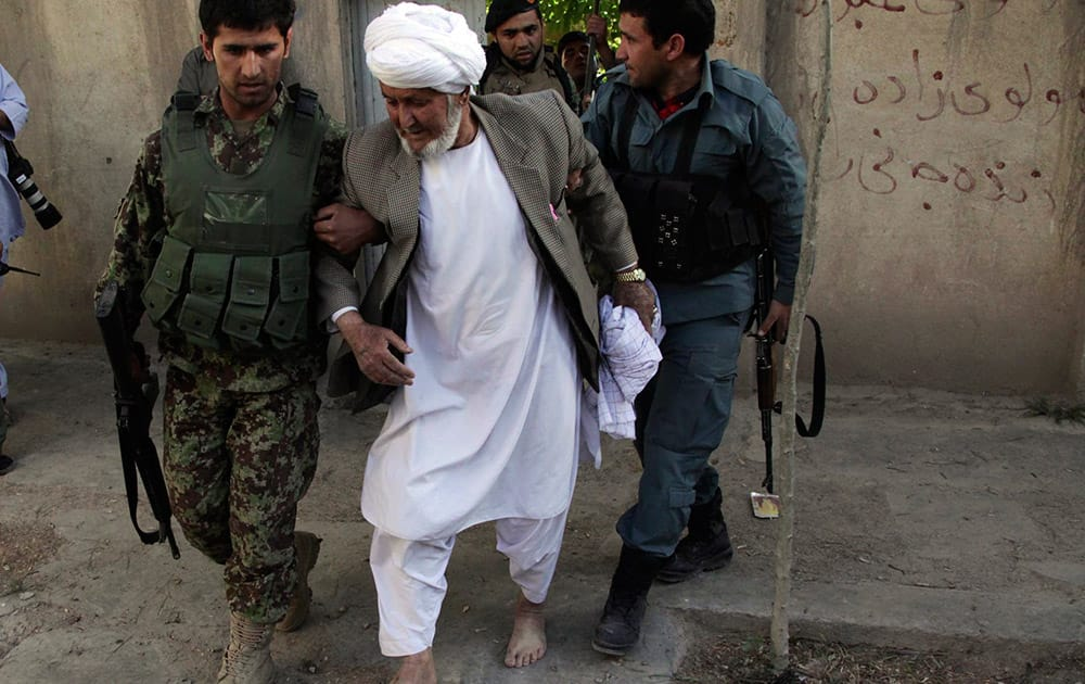 An Afghanistan`s National Army (ANA) soldier assists an old man at the site of a clash between insurgents and security forces at the Indian Consulate in Herat, Afghanistan.