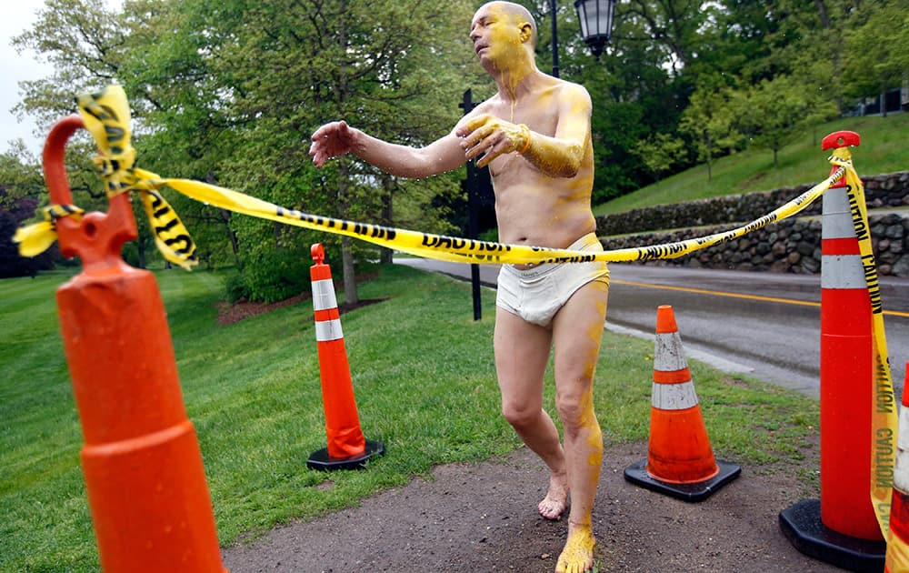 A fiberglass sculpture at Wellesley College, entitled `Sleepwalker,` is surrounded by cones and yellow caution tape after being defaced Tuesday night with yellow paint on its face, left arm, left leg, and a foot.