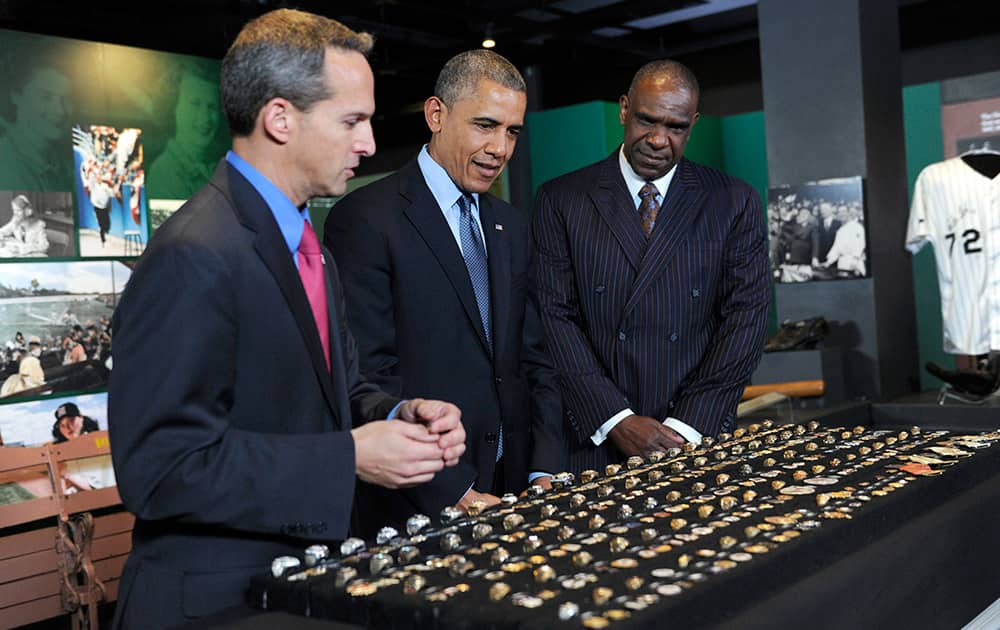 President Barack Obama, accompanied by Baseball Hall of Fame President Jeff Idelson, left, and baseball hall of fame member Andre Dawson, looks over a collection of World Series rings during a tour the Baseball Hall of Fame in Cooperstown, N.Y.