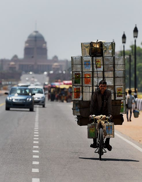 A man carries tin-containers on a bicycle at Rajpath on a hot day in New Delhi.