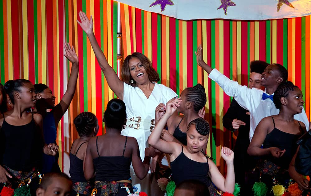 First lady Michelle Obama dances on stage with student performers as she and the President's Committee on the Arts and the Humanities (PCAH) host the White House Talent Show in the East Room of the White House.