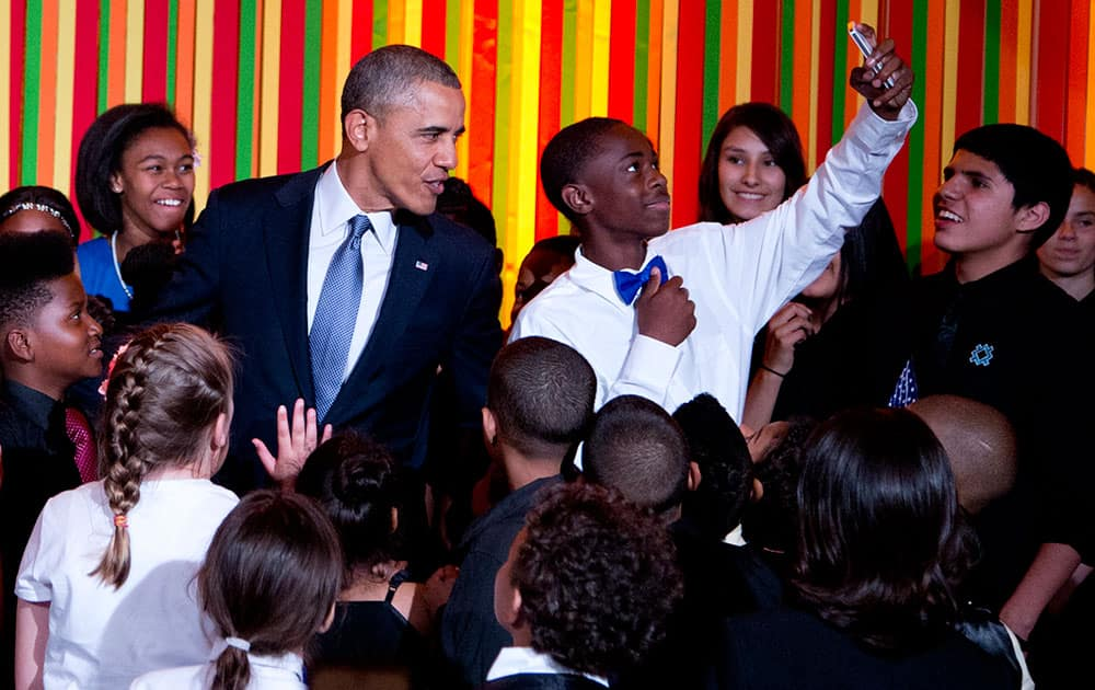 President Barack Obama takes a `selfie` on stage with a a student from the ReNew Cultural Arts Academy, from New Orleans, during the White House Talent Show in the East Room of the White House.