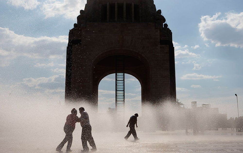 People play in an outdoor fountain on a warm afternoon in Mexico City.