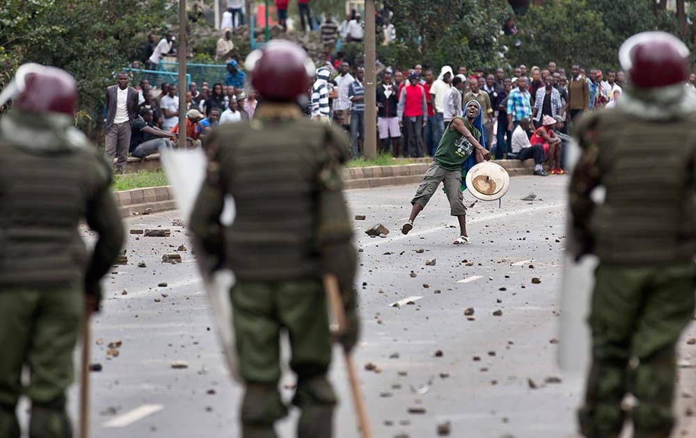A student carrying a makeshift shield throws rocks at riot police as they engage in running battles on the highway next to Nairobi University`s main campus in downtown Nairobi, Kenya.