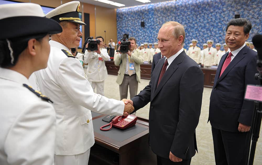 Russia`s President Vladimir Putin shakes hands with a Chinese naval officer, with China`s President Xi Jinping at right, as they open joint naval exercises in Shanghai, China.