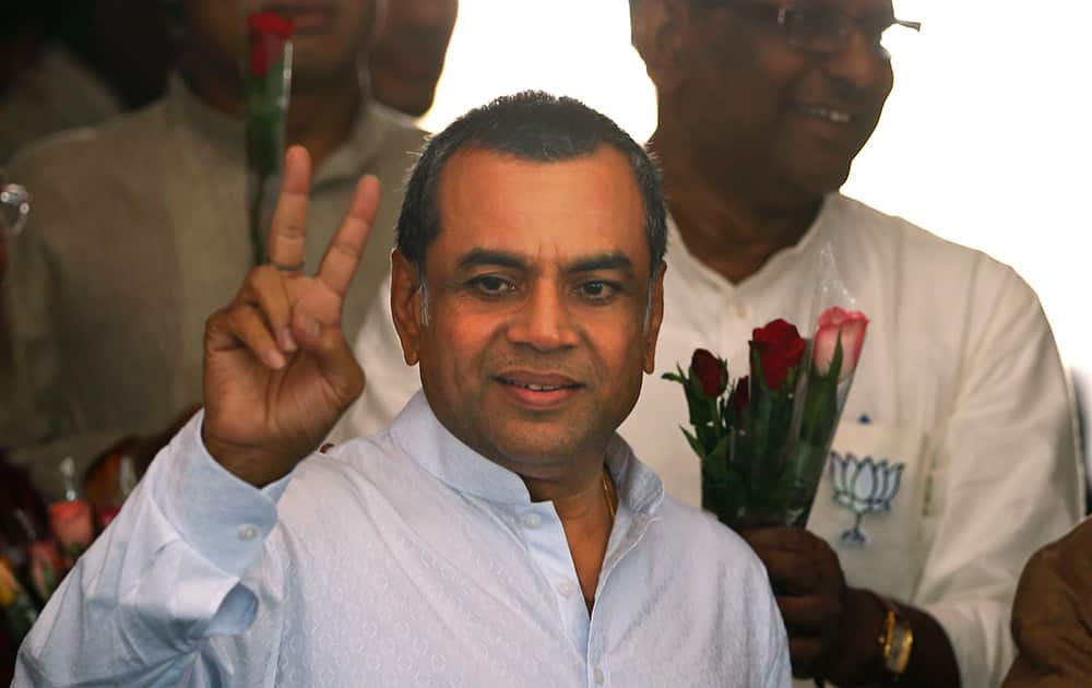 Paresh Rawal displays the victory symbol as he arrives for a meeting of the party`s newly elected lawmakers in New Delhi.