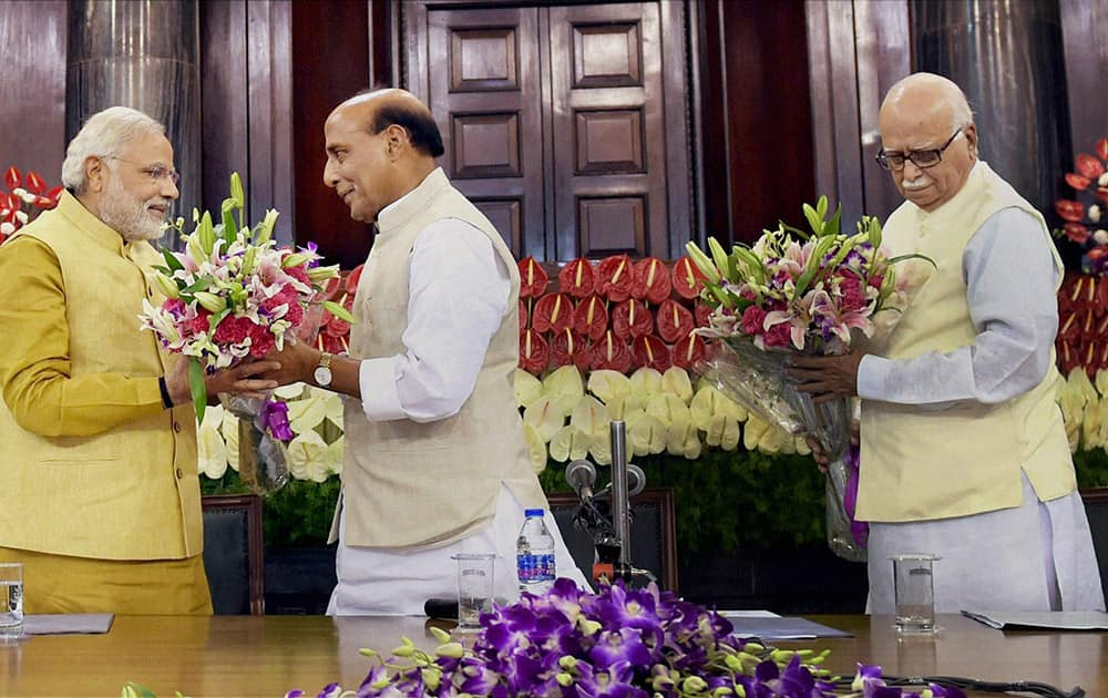 Narendra Modi receives a bouquet of flowers from party President Rajnath Singh, as senior leader Lal Krishna Advani waits to greet Modi during the BJP parliamentary party meeting in New Delhi.