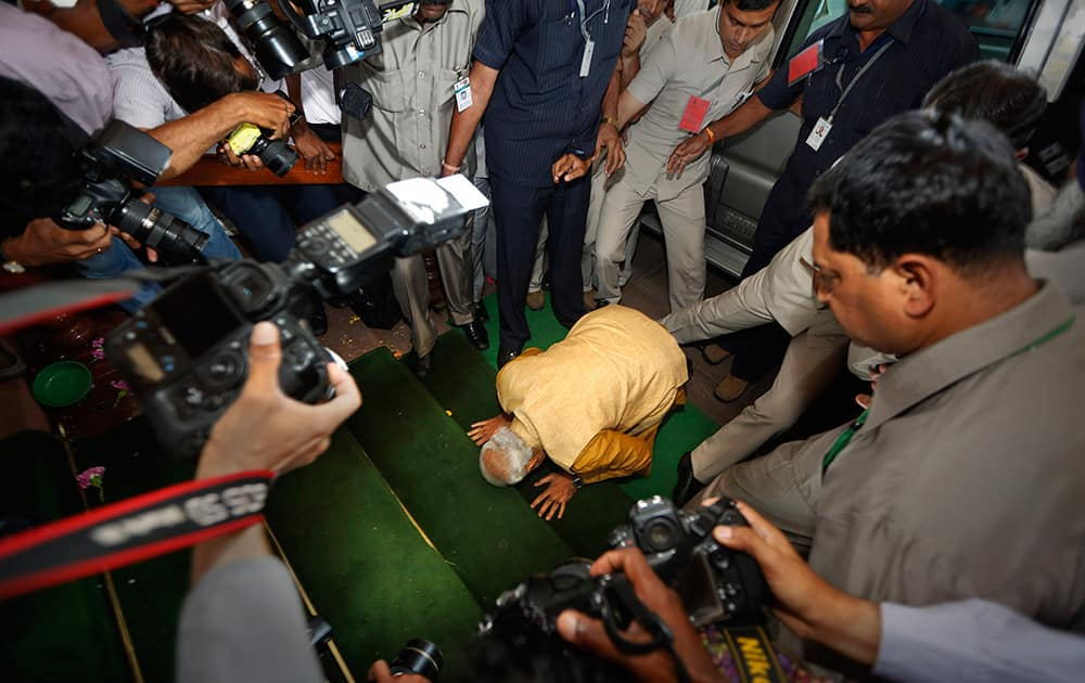 Narendra Modi bends down on his knees on the steps of the Indian parliament building as a sign of respect as he arrives for the BJP parliamentary party meeting in New Delhi.