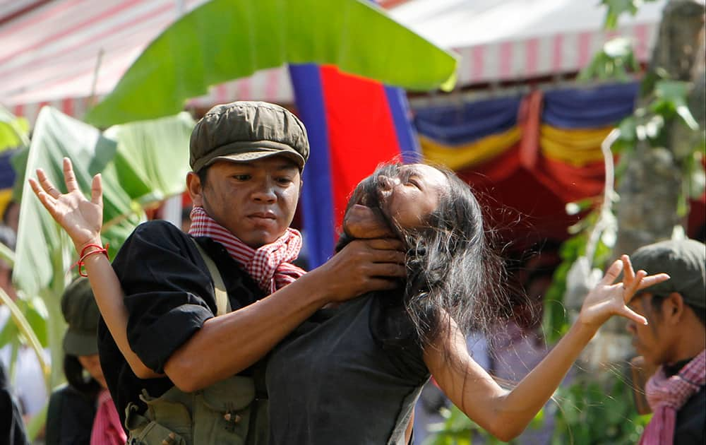 Cambodian students from the Royal University of Fine Arts re-enact torture executed by the Khmer Rouge during their reign of terror in the 1970s to mark the annual Day of Anger at Choeung Ek, a former Khmer Rouge