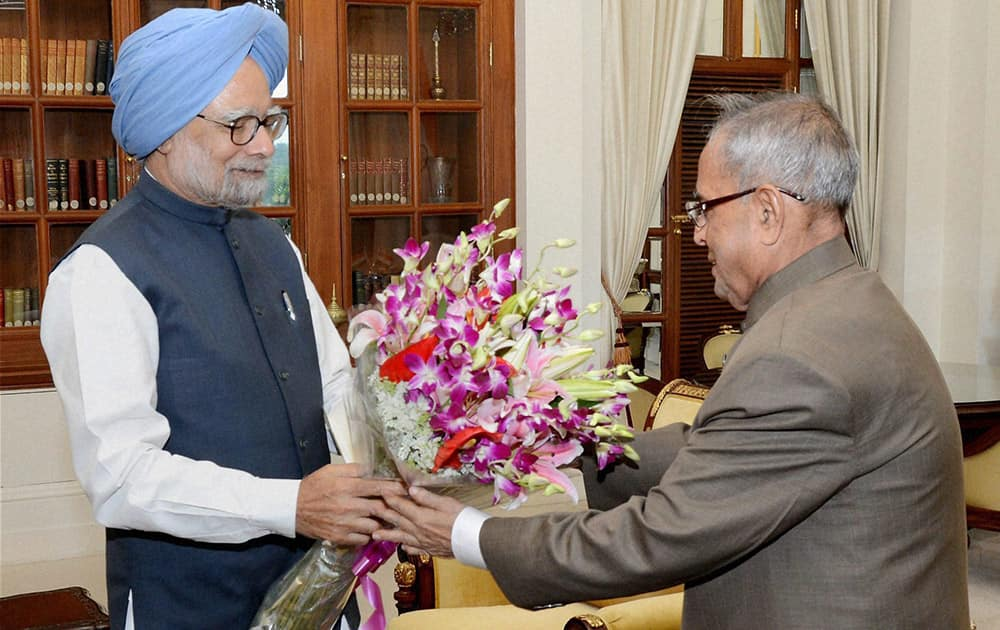 Prime Minister Manmohan Singh presents a bouquet to President Pranab Mukherjee during a meeting to submit his resignation at Rashtrapati Bhavan in New Delhi.