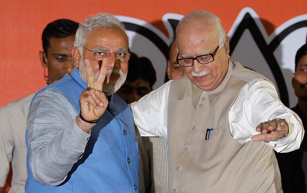 Narendra Modi, left, flashes the victory symbol standing next to senior party leader L.K. Advani at the party headquarters in New Delhi.