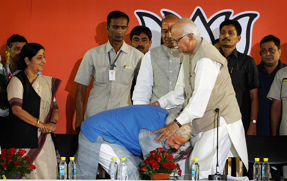 Narendra Modi touches, as an act of respect, the feet of senior party leader L.K. Advani at the party headquarters in New Delhi.
