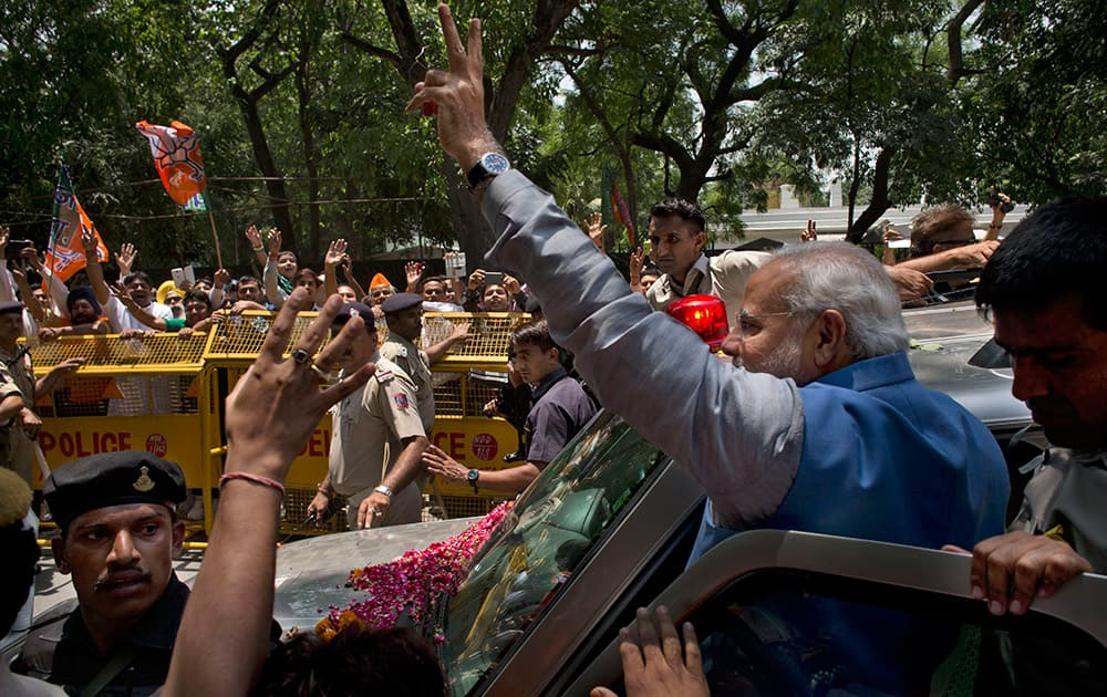 Narendra Modi greets the crowd with a victory symbol outside the party headquarters in New Delhi.