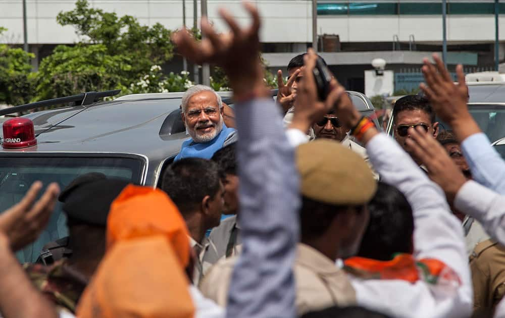 Narendra Modi greets the crowd standing on the footboard of his SUV outside the New Delhi airport.