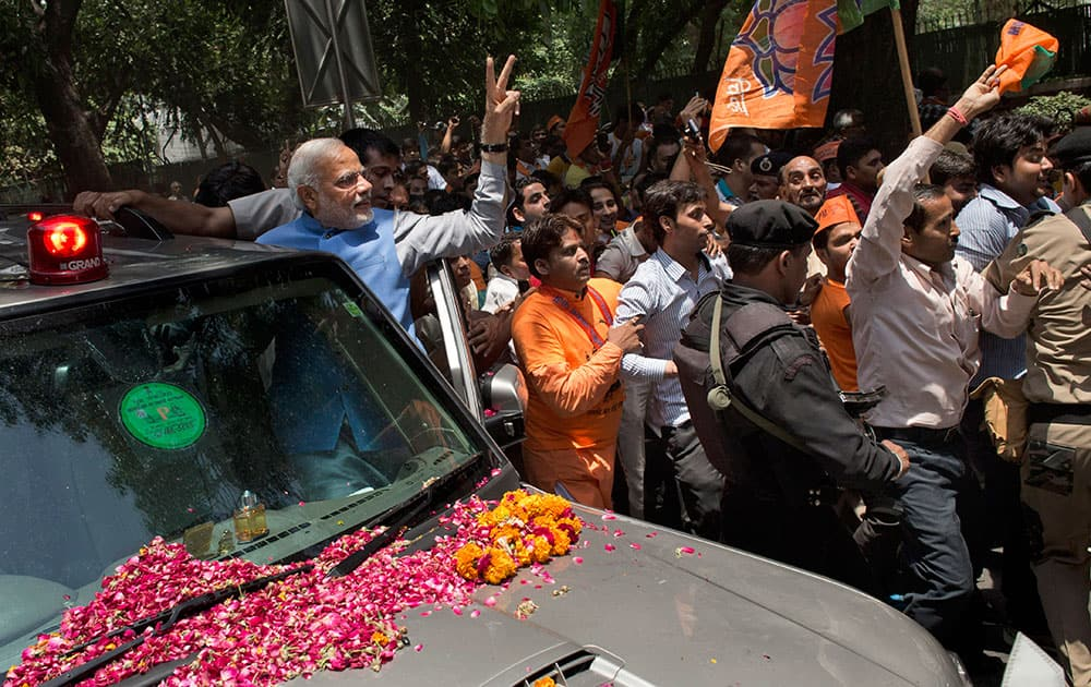 Bharatiya Janata Party (BJP) leader and India`s next prime minister Narendra Modi greets the crowd with a victory symbol outside the party headquarters in New Delhi.
