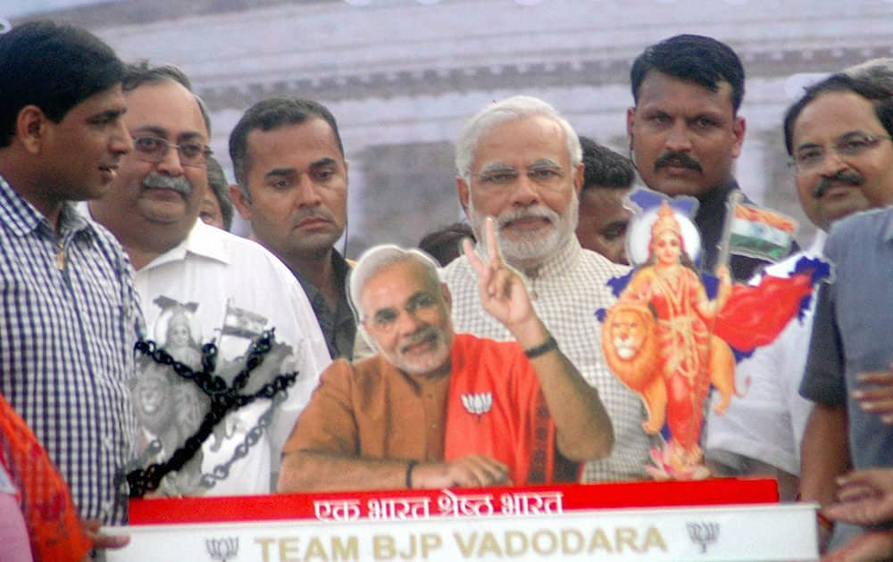 6:35 PM Narendra Modi being presented a memento at a public meeting in Vadodara.