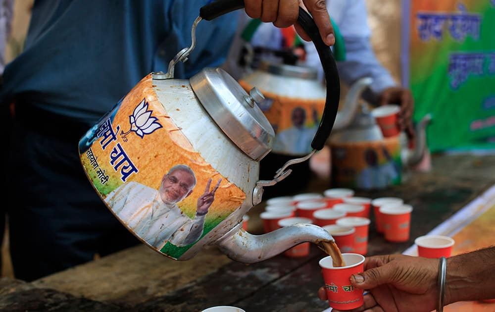 A man pours tea from a kettle with a portrait of Bharatiya Janata Party (BJP) leader and India's next prime minister Narendra Modi, outside the BJP party office in New Delhi.