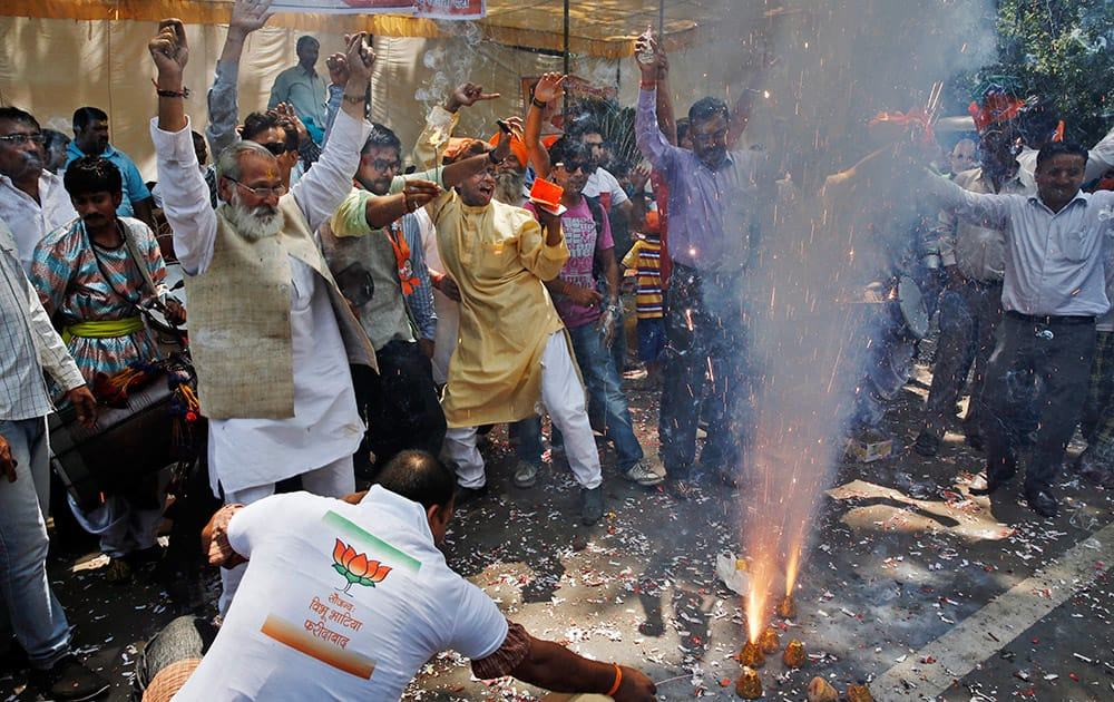 Bharatiya Janata Party (BJP) supporters set off firecrackers and dance to celebrate preliminary results that showed the BJP winning by a landslide, outside the party headquarters in New Delhi.