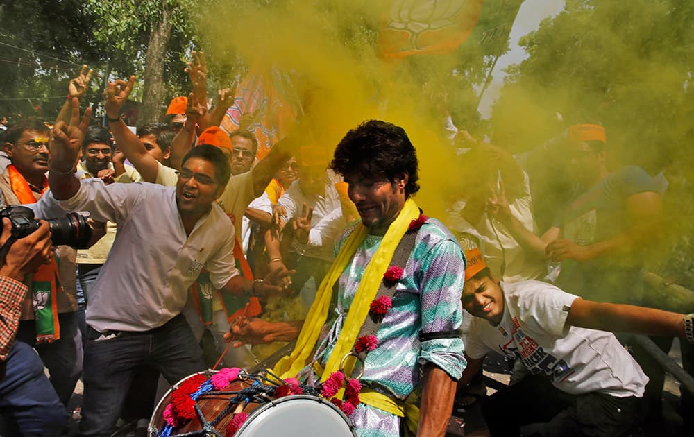 Bharatiya Janata Party (BJP) supporters throw colored powder and dance to celebrate preliminary results that showed the BJP winning by a landslide, outside the party headquarters in New Delhi.