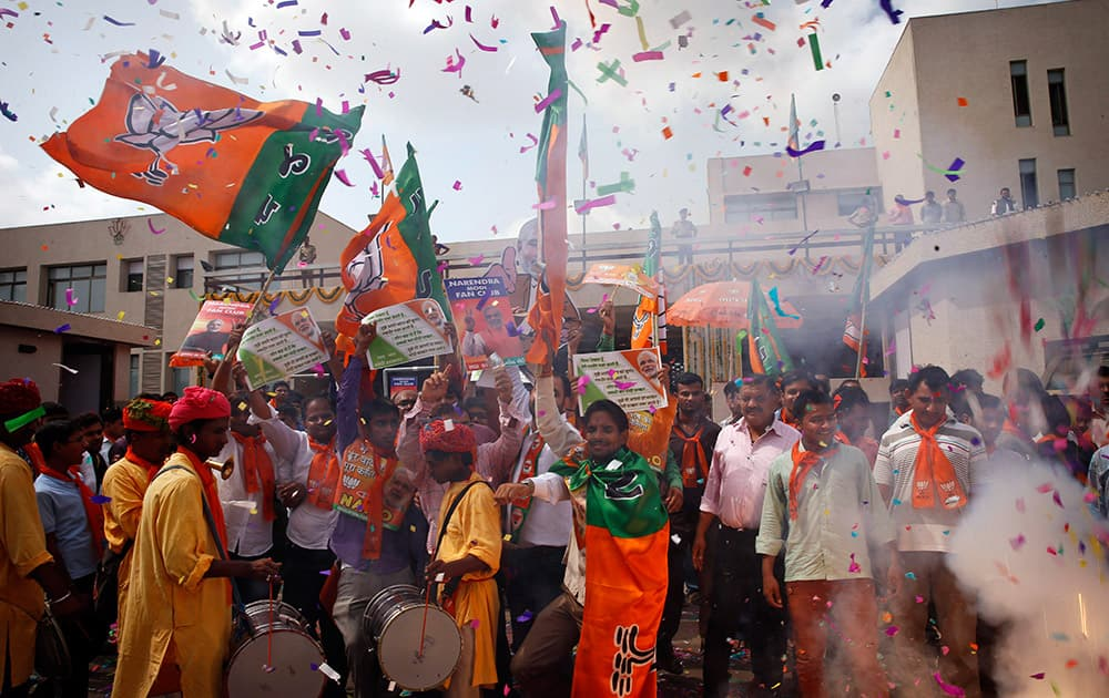 Bharatiya Janata Party (BJP) supporters celebrate outside the party office in Gandhinagar, in the western Indian state of Gujarat.
