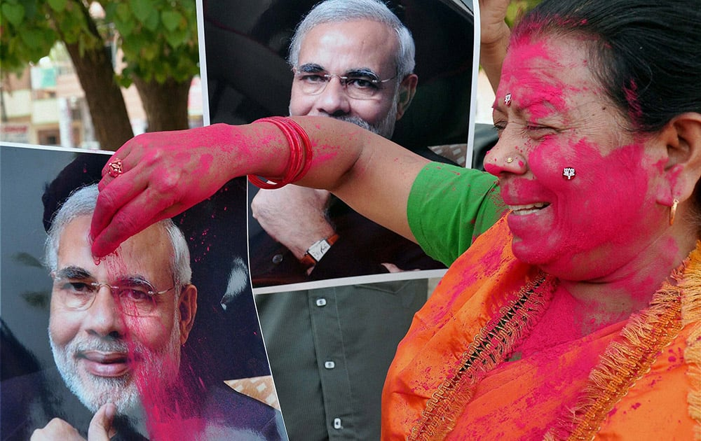 A BJP worker applying gulaal to Nerendra Modi`s picture celebrating the party`s victory in Lok Sabha polls, in Bikaner.